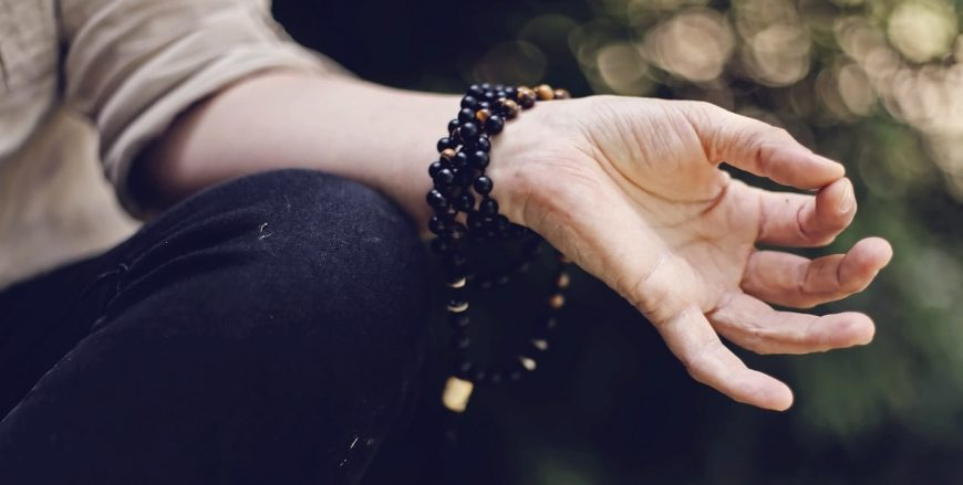 Fingers folded into mudras during mantras